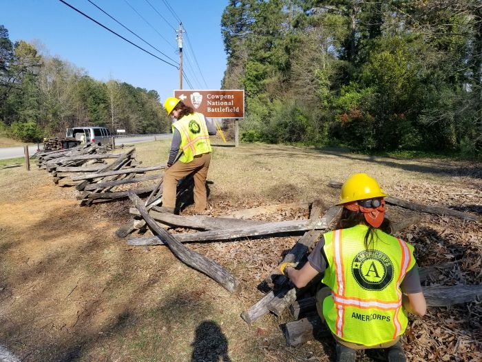 Members working on fencing at Cowpens National Battlefield with park sign in battlefield
